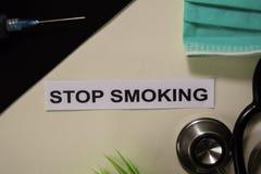 停止抽烟与启发和医疗保健/医疗概念在书桌背景 免版税库存图片