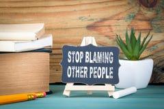 停止责备其他人民 有白垩的小木板在桌上 免版税库存照片