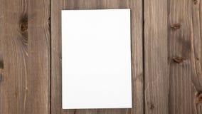 停止运动动画:展开空白的纸片在木背景的模板 股票视频