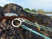 停泊和在Donaghadee c阻塞与绳索的圆环小船的concreted入在岸的岩石在小私有定住 库存图片