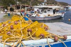 停泊在日出的口岸的捕鱼网和希腊渔船 免版税库存照片