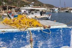 停泊在日出的口岸的捕鱼网和希腊渔船 图库摄影