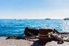 停泊绳索和老系船柱在海水和游艇背景在意大利 库存图片