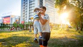 停滞和投掷他笑的3 yearas老矮小的儿子的愉快的微笑的年轻父亲画象在的公园 免版税库存图片