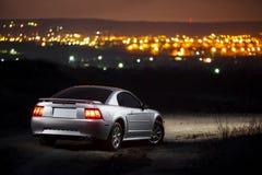 停留反对城市的背景的汽车在晚上 库存图片