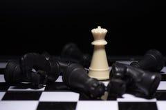 停留反对黑棋子的一棋子 免版税图库摄影