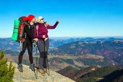 停留和指向在高岩石和山景城的两个远足者有秋季森林的 免版税图库摄影