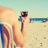 停留在与可乐饮料的海滩的年轻人,被过滤 免版税库存照片