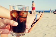 停留在与可乐饮料的海滩的年轻人 免版税库存照片
