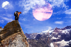 停留在与行星的岩石峭壁的高山登山人在天空 图库摄影