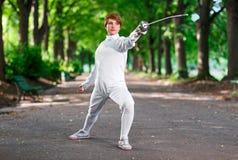 停留在公园胡同的年轻美丽的双刃剑击剑者妇女 图库摄影