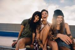 停留在冰鞋公园的三个微笑的女孩 免版税库存照片