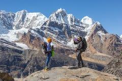 停留在岩石和放松顶部的两个远足者 图库摄影