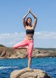 停留在岩石海岸石头的瑜伽姿势的妇女  免版税库存照片