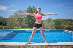 停留在星姿势的运动服的微笑的妇女近的水池 免版税库存图片