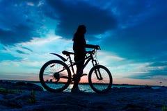 停留在湖的岸的年轻女人有自行车的在太阳 免版税库存照片