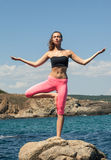 停留在瑜伽姿势的岩石海岸的平静的少妇 库存照片
