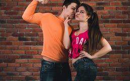 停留在砖墙前面的夫妇 免版税图库摄影