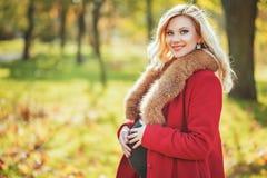 停留在秋天公园的美丽的愉快的孕妇接触她的腹部和享受期望婴孩 免版税图库摄影