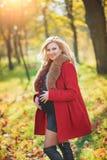 停留在秋天公园的美丽的愉快的孕妇接触她的腹部和享受期望婴孩 图库摄影