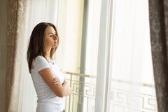 停留在窗口附近和非常严重考虑生活的一名美丽的妇女的画象 库存照片