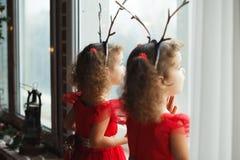 停留在窗口附近的红色礼服的双女孩姐妹等待圣诞老人 与鹿垫铁的逗人喜爱的孩子 免版税库存图片