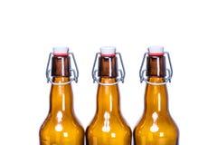停留在行的三个被密封的啤酒瓶 免版税库存照片