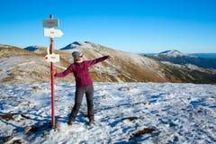 停留在道路标志和赞赏的风景看法的女性远足者在冬天山 免版税库存照片