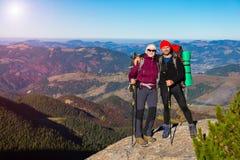 停留在高岩石和山景城的两个远足者有秋季森林的 库存图片