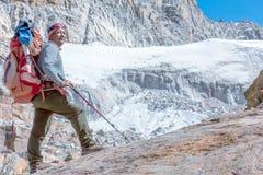 停留在高岩石顶部的尼泊尔山指南 免版税库存图片