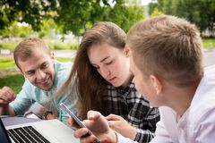 停留户外的三个年轻朋友serfing的互联网 库存图片