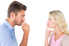停留年轻的夫妇沈默与在嘴唇的手指 图库摄影