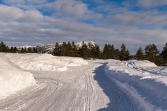 停车场在冬天,从除雪机的随风飘飞的雪,在Jarnsverk停车处在Brokke Setesdal,挪威 免版税库存照片