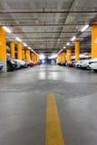 停车库,地下与一些辆停放的汽车的内部 免版税图库摄影