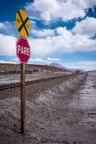 停车牌(削去)在一个落寞风景的铁路交叉 库存图片