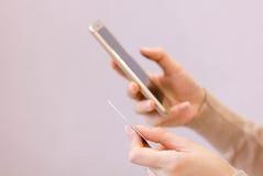 停滞信用卡和关闭的手使用流动巧妙的电话与早晨,网上购物,网上付款, m 免版税库存图片
