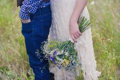 年轻健康一个婚礼礼服人的夫妇时兴的女孩站立与明亮的花花束的格子花呢上衣的在手上, 免版税库存照片