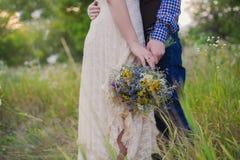 年轻健康一个婚礼礼服人的夫妇时兴的女孩站立与明亮的花花束的格子花呢上衣的在手上, 库存图片
