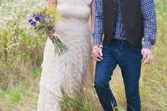 年轻健康一个婚礼礼服人的夫妇时兴的女孩站立与明亮的花花束的格子花呢上衣的在手上, 免版税库存图片