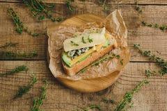 健康三明治用鲕梨、乳酪和草本 在木背景 库存图片