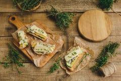 健康三明治用鲕梨、乳酪和草本 在木背景 库存照片