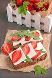 健康三明治用黑麦面包、新鲜的草莓、芝麻菜和软干酪在羊皮纸 免版税库存照片