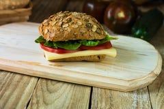 健康三明治用乳酪,蕃茄,在木切板,土气样式的莴苣 免版税图库摄影