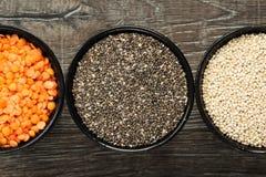 健康五谷的不同的类型在碗的在木背景 免版税库存图片