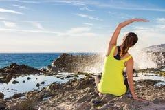 健康亚裔在佩带黄色上面的海滩的女子实践的瑜伽 图库摄影