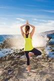 健康亚裔在佩带黄色上面的海滩的女子实践的瑜伽 免版税图库摄影