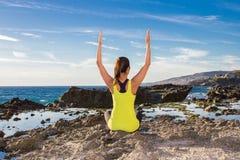 健康亚裔在佩带黄色上面的海滩的女子实践的瑜伽 免版税库存图片