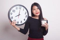 健康亚裔牛奶举行时钟妇女水杯  免版税图库摄影
