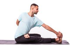 年轻健康人做在白色背景的瑜伽 免版税库存照片