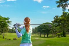健康体育 做高尔夫球摇摆发球区域在绿色平衡的时间的亚裔运动的女子高尔夫球运动员球员,她据推测行使 库存图片